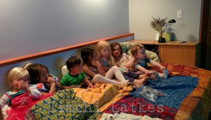 Seven children lined up on a bed, all looking off in the same direction, watching TV. The children range in age from one to six.