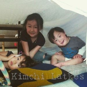 LP with his two big sisters under a fort made of a white sheet and various tables and chairs. LP is tilting his head and smiling.