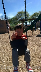 LP in a swing, waving at the camera. He's smiling. It is a sunny day, and the park climbing structure is visible in the background.