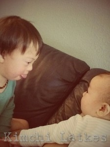 2yo with Down syndrome (LP) in a green pajama shirt, sticking out his tongue. His 4 month old sister (Sparrow) watches.