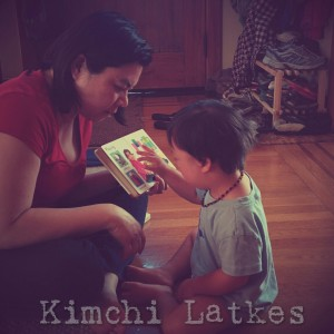 A woman sitting cross-legged, holding a board book in front of LP, who is pointing to different pictures on the page.
