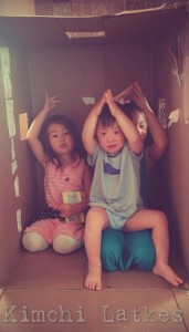 "LP and his sisters in a large cardboard box, all doing the ASL sign for ""shark"" as part of the Slippery Fish song. LP is sitting on one sister's lap only wearing a shirt and underwear."